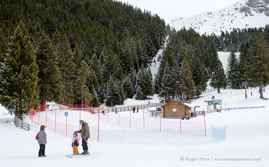 Grandparents with young child skier in debutant area with ski lift