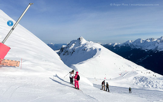 Ski instructor and skiers on mountainside