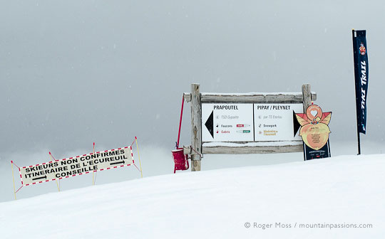 ski piste signs above Prapoutel with falling snow