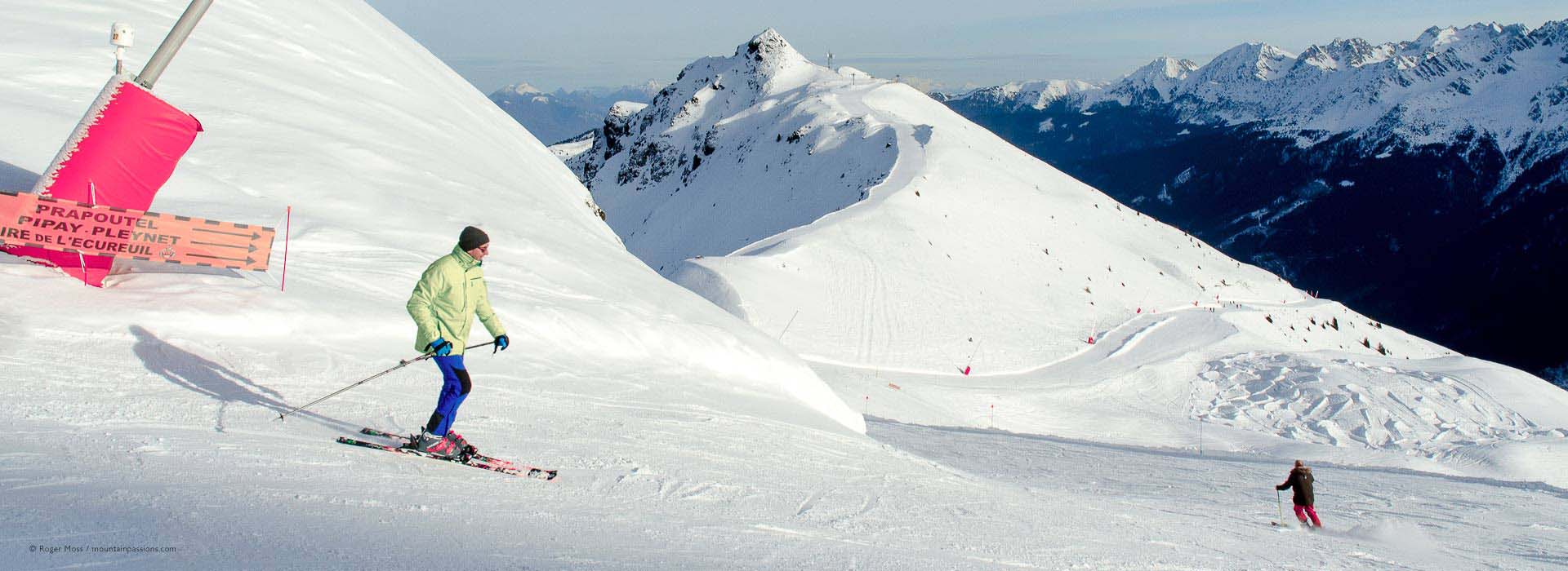 Skiers on piste with wide mountain view